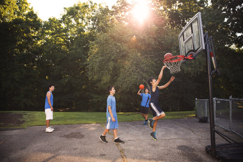 Players playing basketball at court against trees on sunny day - CAVF40388