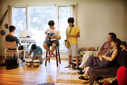 Parents looking at sons performing with music instruments in living room - CAVF40406