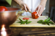 Midsection of woman cutting tomato slices by mint leaves on cutting board - CAVF40412