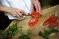 Cropped image of woman cutting tomato slices by mint leaves on cutting board - CAVF40415