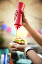 Cropped image of woman pouring ketchup on hamburger at garden party - CAVF40430