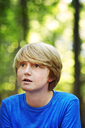 Thoughtful boy looking away while standing in forest - CAVF40463