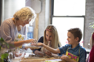 Children with grandmother preparing cookies in kitchen - CAVF40475