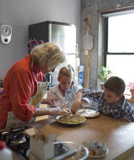 Children with grandmother garnishing food in kitchen - CAVF40487
