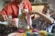 Woman with grandson filling cupcake holders in kitchen - CAVF40490