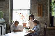 Mother assisting children in doing homework while sitting at table - CAVF40496