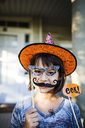 Portrait of smiling girl holding props enjoying during Halloween party - CAVF40544