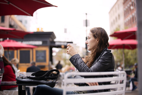 Thoughtful woman holding coffee cup while sitting at sidewalk cafe in city - CAVF40559