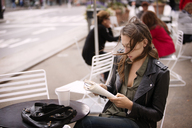 Woman in jacket reading book while sitting at sidewalk cafe - CAVF40562