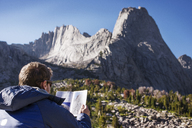 Rear view of hiker reading map against mountain - CAVF40574