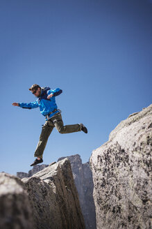 Hiker jumping on rock formations against clear blue sky - CAVF40586