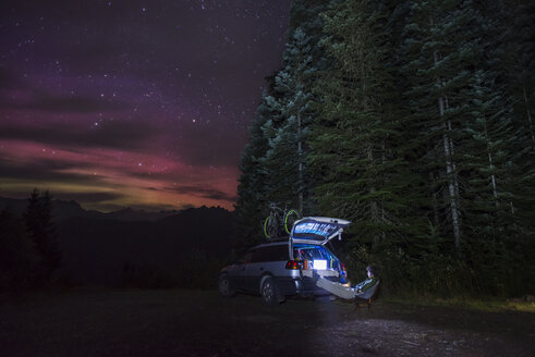 Hiker looking at laptop while resting by car in forest against star field - CAVF40688