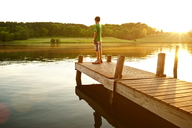 Boy standing on jetty over lake during sunny day - CAVF40769