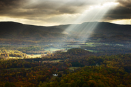Scenic view of sunlight streaming through cloudy sky over mountain - CAVF40793
