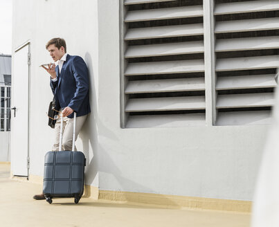 Businessman with rolling suitcase using smartphone at parking garage - UUF13419
