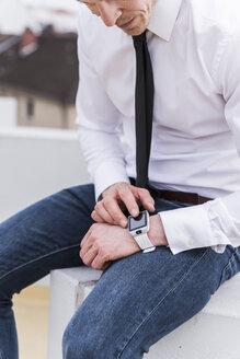 Businessman sitting outdoors using smartwatch - UUF13428