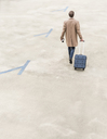 Rear view of businessman with rolling suitcase walking at parking garage - UUF13437