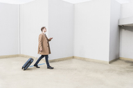 Businessman with rolling suitcase and cell phone at parking garage - UUF13440