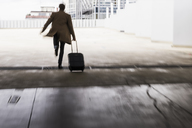 Businessman with rolling suitcase in a hurry at parking garage - UUF13446