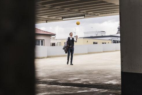 Businessman throwing up basketball at parking garage - UUF13449