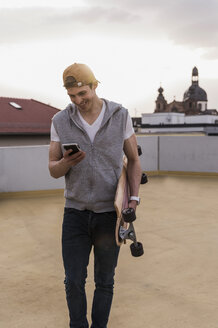 Smiling man with cell phone and skateboard walking at parking garage - UUF13461