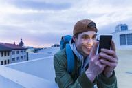 Smiling man looking at shining smartphone at dusk - UUF13464