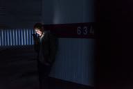 Smiling man looking at shining smartphone in parking garage - UUF13467
