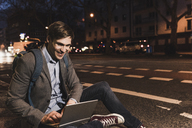 Smiling businessman using laptop on urban street at night - UUF13473