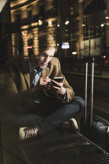 Businessman using cell phone at tram station at night - UUF13476