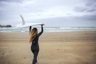Woman carrying surfboard while walking on beach against sky - CAVF40835
