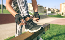 Low section of woman tying shoelaces while exercising at park - CAVF40850