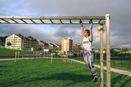 Full length of woman exercising on monkey bars at park - CAVF40859