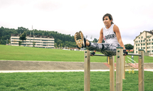 Full length of woman exercising on parallel bars at park - CAVF40862