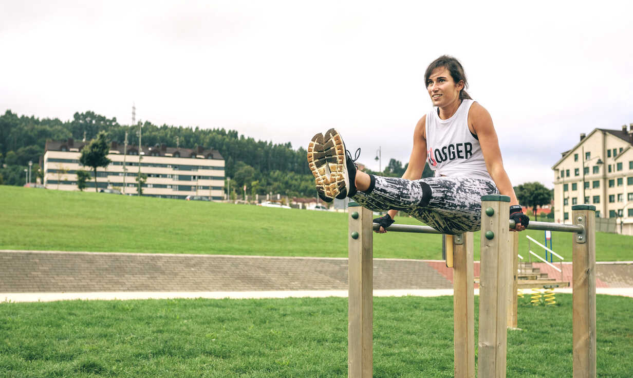 Full length of woman exercising on parallel bars at park - CAVF40862 - Cavan Images/Westend61