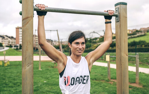 Confident woman holding gymnastics bar while exercising at park - CAVF40865