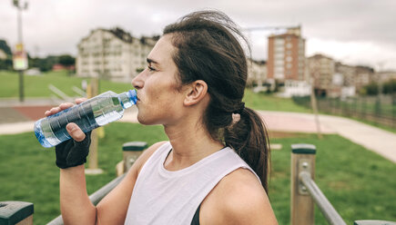 Woman drinking water while exercising at park - CAVF40877