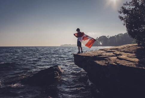 Full length of boy holding Canadian Flag while standing on cliff against sea and sky during sunny day - CAVF40910
