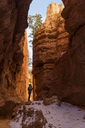 Female hiker standing by rock formations at Bryce Canyon National Park - CAVF40928