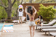 Friends playing with beach ball at poolside - CAVF41018