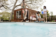 Excited friends looking at man jumping in swimming pool at tourist resort - CAVF41024