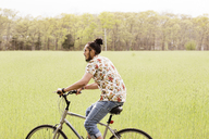 Young man riding bicycle on grassy field - CAVF41036