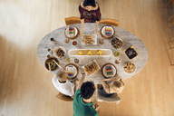 Overhead view of friends arranging food on dining table - CAVF41141