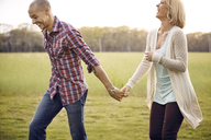 Couple holding hands while walking on field - CAVF41231