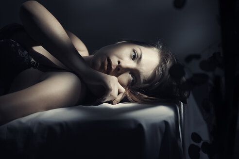 Thoughtful woman looking away while lying on bed at home - CAVF41251