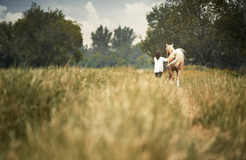 Rear view woman and horse walking on grassy field at countryside - CAVF41257