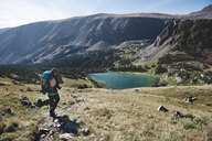 Woman hiking on mountain by lake - CAVF41401