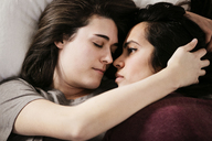 Overhead view of loving lesbian couple lying on bed - CAVF41425