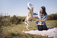 Woman giving frisbee to playful dog at park against sky - CAVF41506