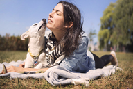 Loving woman and dog lying on blanket at park - CAVF41509