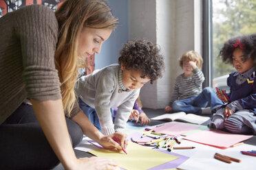 Teacher drawing with students on floor at preschool - CAVF41545